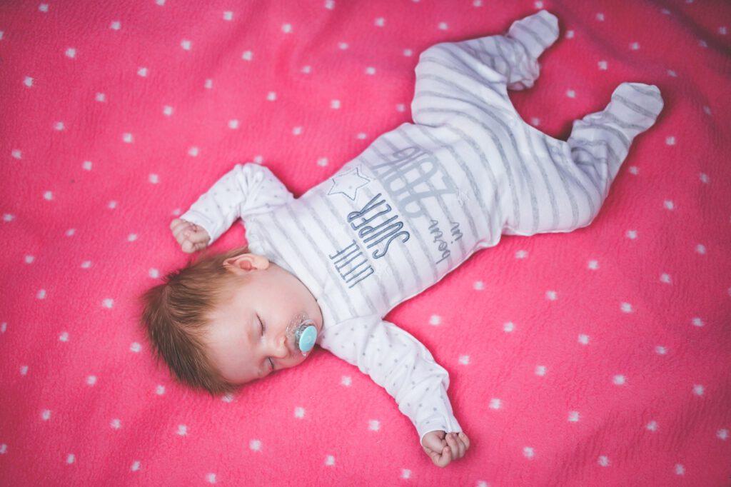 Baby schläft auf rosa Kuscheldecke